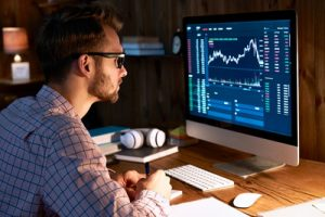 man looking at share prices on a computer screen