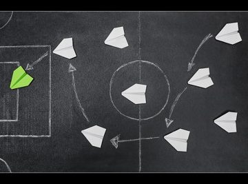 football pitch chalk board with paper airplanes last one green