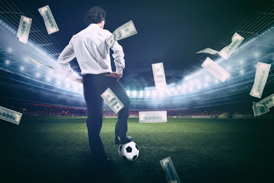 business man on football pitch money raining down